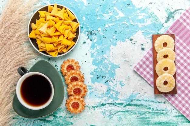 Bovenaanzicht kleine pittige chips met gezouten crackers en koekjes op blauwe achtergrond chips snack kleur scherpe calorie