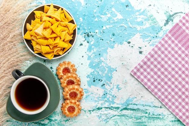 Bovenaanzicht kleine pittige chips met gezouten crackers en koekjes op lichtblauwe achtergrond chips snack kleur knapperige calorie