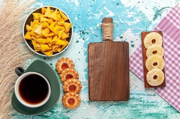 Bovenaanzicht kleine pittige chips met gezouten crackers en koekjes op lichtblauwe achtergrond koekjeskoekje zoete suiker thee thee