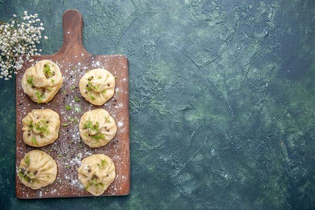 Bovenaanzicht kleine rauwe dumplings met vlees binnen op donkerblauwe ondergrond deeg keuken schotel cake vlees diner maaltijd koken vrije ruimte