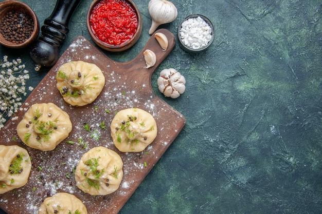Bovenaanzicht kleine rauwe knoedels met tomatensaus op donkerblauwe achtergrond koken diner deeg gerecht maaltijd keuken vlees