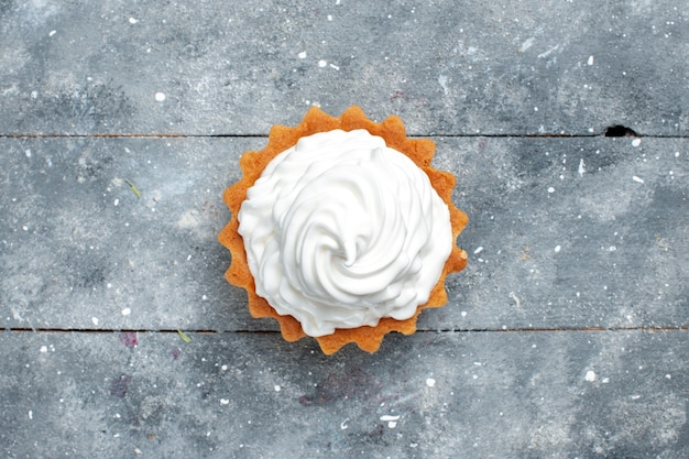 Bovenaanzicht kleine romige cake heerlijk gebakken geïsoleerd op de grijze achtergrond cake koekje zoete suiker foto