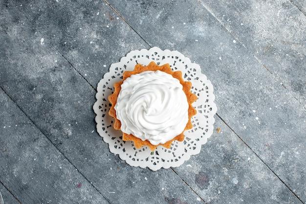 Bovenaanzicht kleine romige cake heerlijk gebakken geïsoleerd op de grijze lichte achtergrond cake biscuit suiker room bakken
