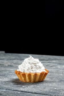 Bovenaanzicht kleine romige cake heerlijk gebakken geïsoleerd op de grijze tafel cake biscuit zoete foto crème