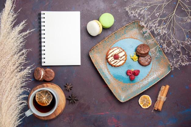 Bovenaanzicht kleine romige cake met chocoladekoekjes en kopje thee op het donkere oppervlak biscuit zoete taart suiker koekjes cake