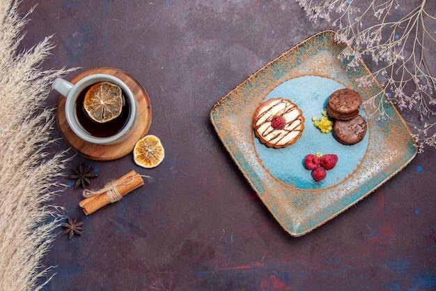 Bovenaanzicht kleine romige cake met chocoladekoekjes en kopje thee op het donkere oppervlak koekjescake zoete taart suikerkoekje