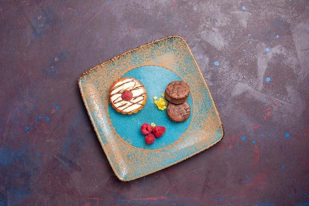 Bovenaanzicht kleine romige cake met chocoladekoekjes in een bord op een donkere ondergrond, biscuitsuikercake, zoete taart