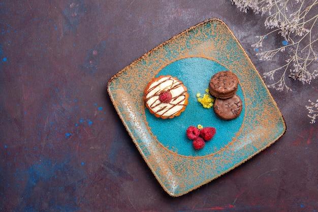 Bovenaanzicht kleine romige cake met chocoladekoekjes op donkere oppervlaktekoekjescake, zoete taartsuikerkoekje