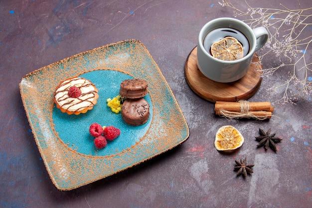 Bovenaanzicht kleine romige cake met chocoladekoekjes op donkere oppervlaktekoekjescake, zoete taartsuikerkoekjes