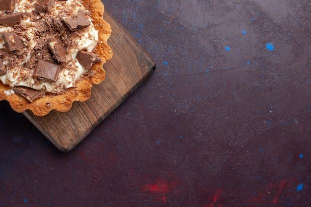 Bovenaanzicht kleine romige cake met chocoladestukjes op een donkere ondergrond