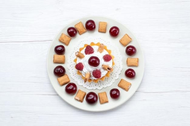 Bovenaanzicht kleine romige cake met frambozen en kleine koekjes op de witte achtergrond fruitcake zoete suiker crème kers