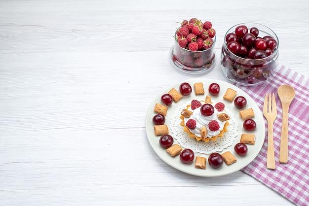 Bovenaanzicht kleine romige cake met frambozen en kleine koekjes samen met kersen op het wit-lichte bureau fruitcake zoete bessenroom kers