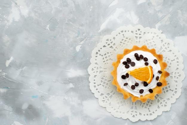 Bovenaanzicht kleine romige cake met gedroogd fruit en sinaasappelschijfje op de grijze oppervlakte zoete room
