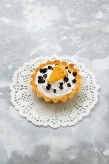 Bovenaanzicht kleine romige cake met gedroogd fruit en sinaasappelschijfje op de lichttafel