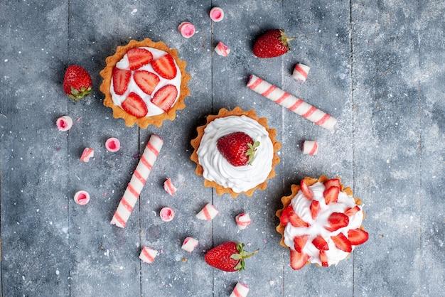 Bovenaanzicht kleine romige cake met gesneden en verse aardbeien samen met stoksnoepjes op de grijze achtergrond fruit zoete kleurenfoto bakken
