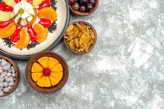 Bovenaanzicht kleine romige cake met gesneden fruit en rozijnen op wit oppervlak fruit zoete taart taart suiker biscuit