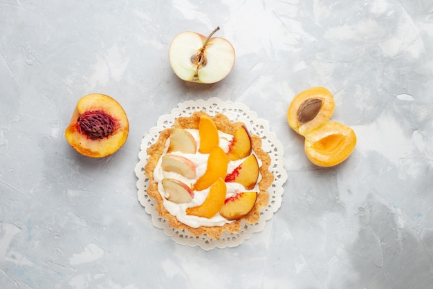 Bovenaanzicht kleine romige cake met gesneden fruit en witte room op de wit-lichte tafel fruitcake zoete koekkoekjes bakken