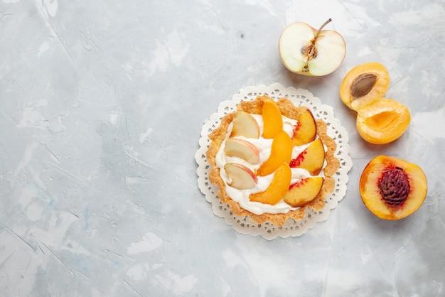 Bovenaanzicht kleine romige cake met gesneden fruit en witte room op de wit-lichte vloer fruitcake zoet koekje koekjes bakken