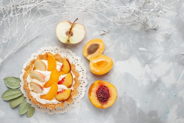 Bovenaanzicht kleine romige cake met gesneden fruit en witte room samen met verse abrikozen en perziken op het witte licht bureau fruit cake biscuit cookie