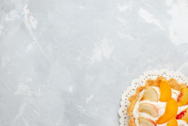 Bovenaanzicht kleine romige cake met gesneden fruit erop op het witte bureau fruitcake zoete koekjessmaak