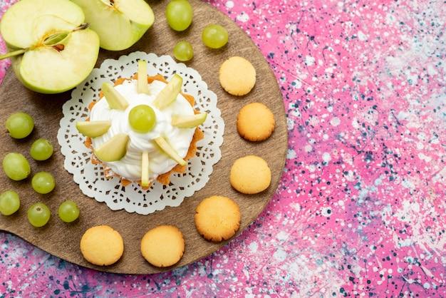 Bovenaanzicht kleine romige cake met gesneden fruit koekjes druiven op de gekleurde achtergrond cake zoete suiker bakken kleurenfoto