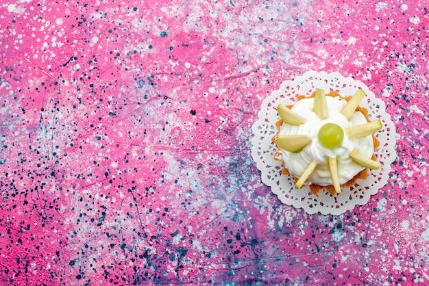 Bovenaanzicht kleine romige cake met gesneden fruit op de gekleurde achtergrond cake zoete suiker bak kleur