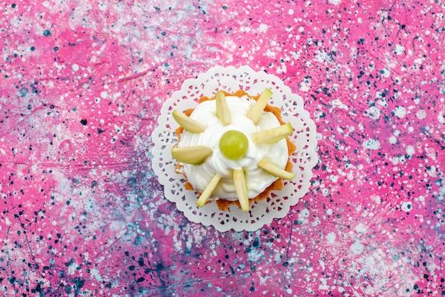 Bovenaanzicht kleine romige cake met gesneden fruit op de gekleurde achtergrond cake zoete suiker bakken kleurenfoto