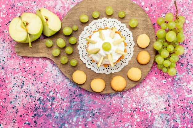 Bovenaanzicht kleine romige cake met gesneden fruit op de gekleurde bureau cake zoete suiker bak foto