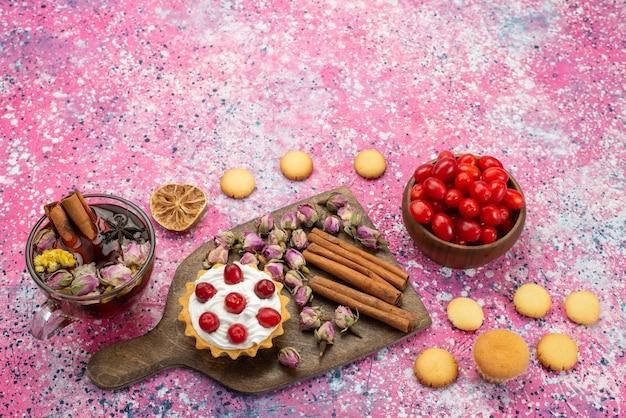 Bovenaanzicht kleine romige cake met kaneelkoekjes, thee en rood fruit op het paarse bureau zoete fruit