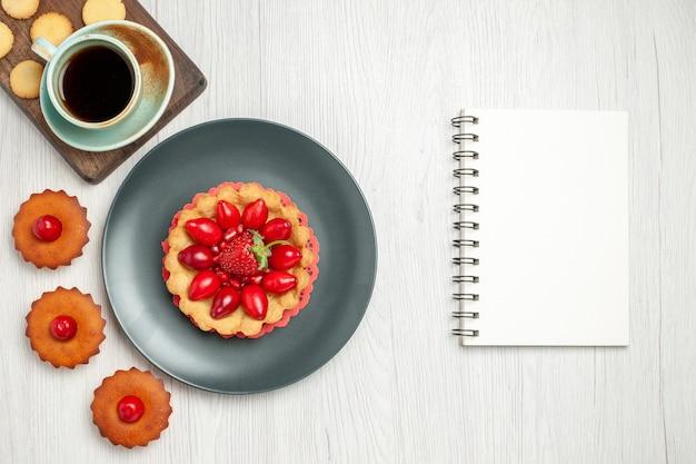 Bovenaanzicht kleine romige cake met kopje thee op het witte bureau