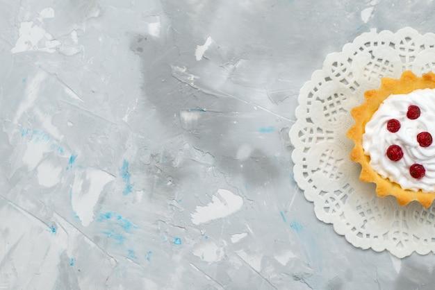 Bovenaanzicht kleine romige cake met rood fruit op het grijze oppervlak zoet