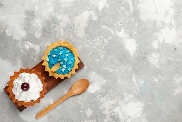 Bovenaanzicht kleine romige cake met room en houten lepel op de lichte achtergrond fruitcake zoete bakroom