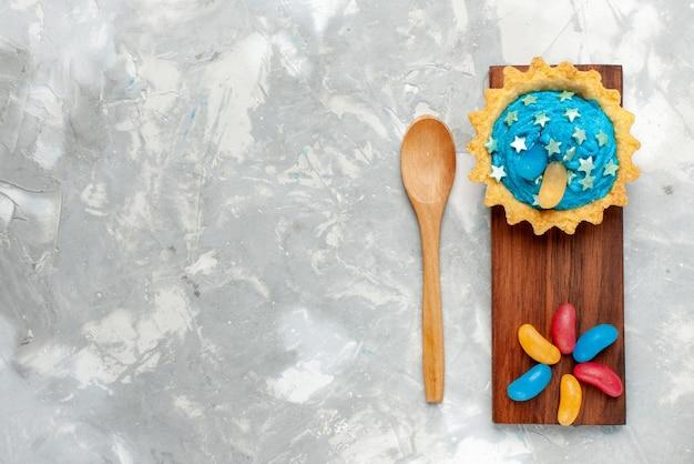 Bovenaanzicht kleine romige cake met snoepjes op de lichte achtergrond cake zoete bak kandijsuiker