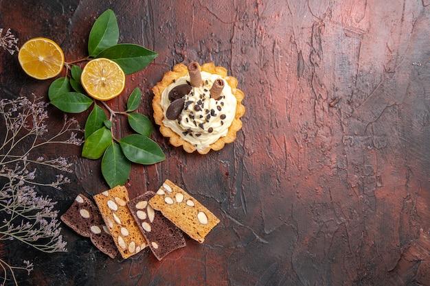 Bovenaanzicht kleine romige cake met taart op donkere tafel zoete koekje