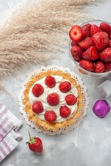 Bovenaanzicht kleine romige cake met verse rode aardbeien en chocolade snoepjes cake op de wit-lichte tafel cake fruit bessen biscuit crème