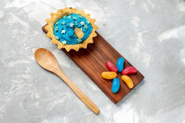 Bovenaanzicht kleine romige cake op de lichte achtergrond cakekoekje zoete taartkleur