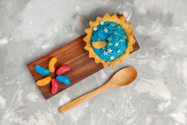 Bovenaanzicht kleine romige cake op de witte bureaucake bak zoete suikercrème