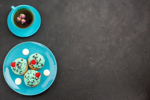 Bovenaanzicht kleine romige taarten heerlijke snoepjes met kopje thee op donkergrijs oppervlak thee crème cake biscuit dessert kleur