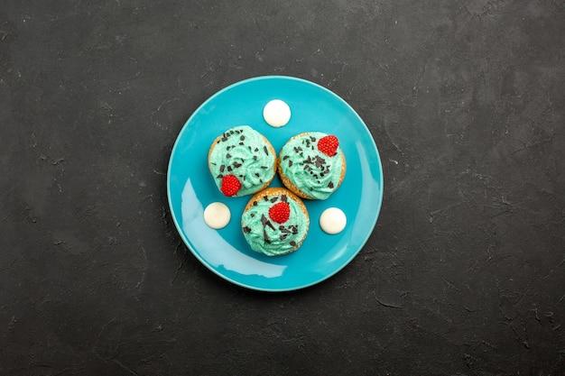 Bovenaanzicht kleine romige taarten heerlijke snoepjes voor thee binnen plaat op donkere oppervlakte crème cake biscuit dessert thee kleur