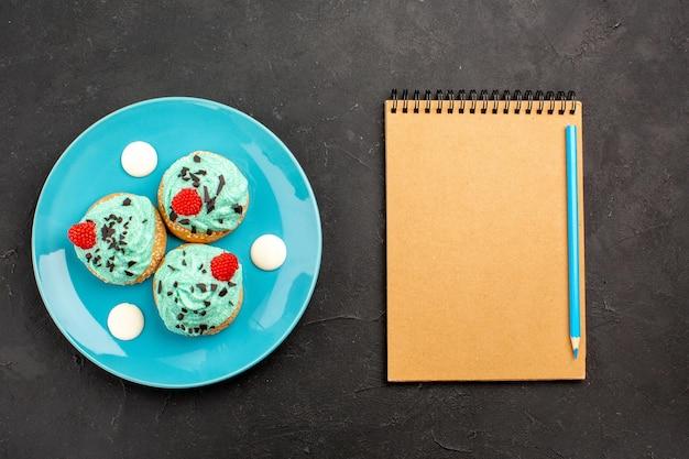 Bovenaanzicht kleine romige taarten heerlijke snoepjes voor thee binnen plaat op donkere oppervlakte thee crème cake biscuit dessert kleur