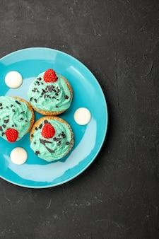 Bovenaanzicht kleine romige taarten heerlijke snoepjes voor thee binnen plaat op donkergrijs oppervlak crème cake biscuit dessert thee kleur