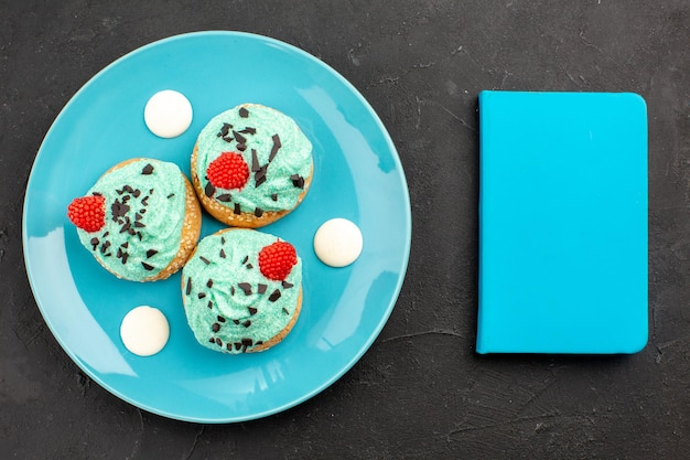 Bovenaanzicht kleine romige taarten heerlijke snoepjes voor thee binnen plaat op het donkergrijze oppervlak thee crème cake biscuit dessert kleur