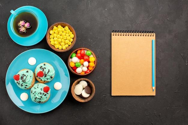 Bovenaanzicht kleine romige taarten met kopje thee en snoep op het donkere oppervlak thee crème cake biscuit dessert kleur