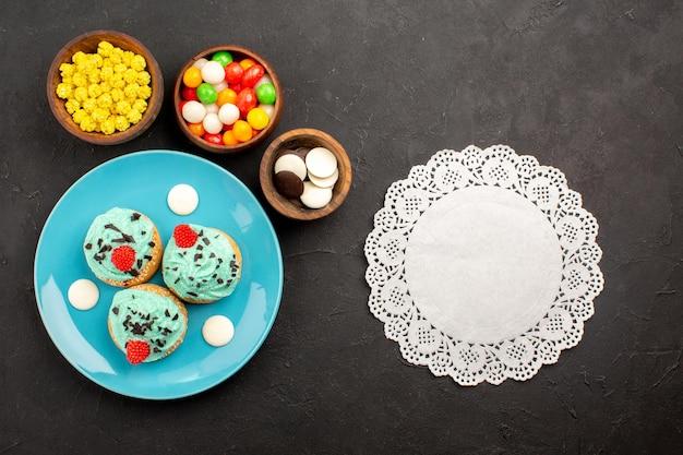 Bovenaanzicht kleine romige taarten met snoepjes op donkere oppervlakte dessert cake biscuit kleur snoep crème