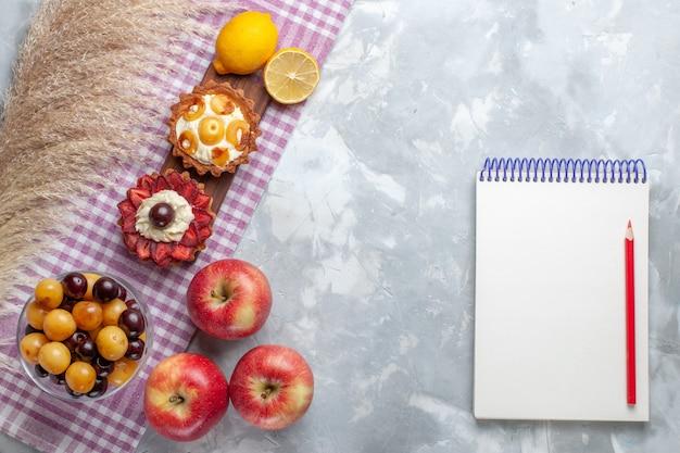 Bovenaanzicht kleine romige taarten met verse rode appels, kersen en citroen op het witte bureau fruitcake koekjesroom zoet