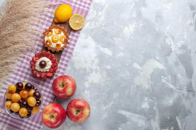Bovenaanzicht kleine romige taarten met verse rode appels op wit bureau fruitcake koekjesroom zoet
