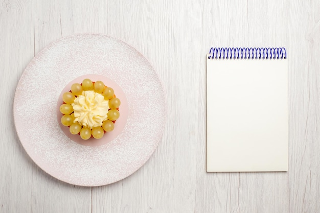 Bovenaanzicht kleine slagroomtaart met druiven op wit bureau fruitcake dessert taartkoekjes