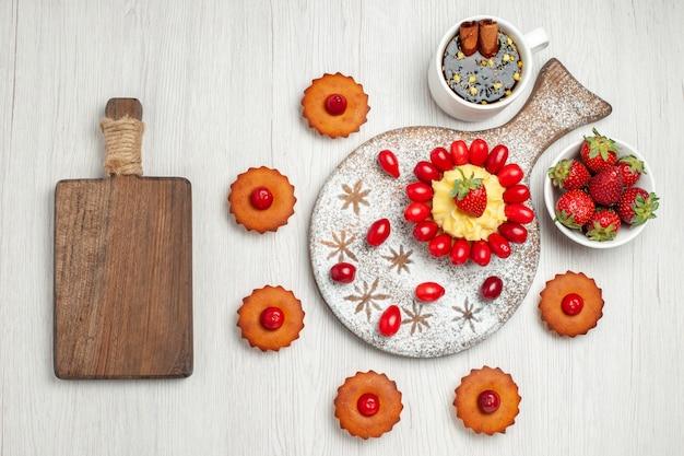 Bovenaanzicht kleine slagroomtaart met fruit en gebak op wit bureau