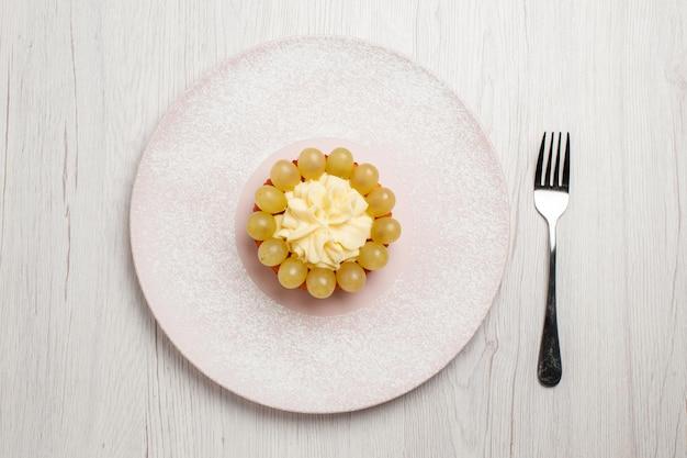 Bovenaanzicht kleine slagroomtaart met verse druiven op witte oppervlakte taart fruit cake dessert biscuit cookie