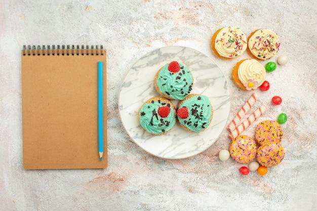Bovenaanzicht kleine slagroomtaarten met kleurrijke snoepjes en koekjes op wit oppervlak goodie regenboog snoep dessert kleur cake